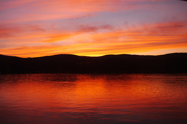 During a sunset, hills are silhouetted between a pink, blue, and yellow sky and a lake glowing orange
