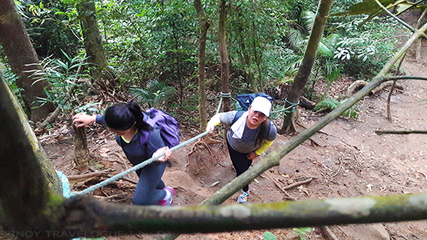 Hiking with help of ropes installed along the steep trail