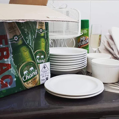 Benchtop with a red, gold and green beer carton on top of it, opened, with a length of 'fragile' tape on the side. Next to the carton are two stacks of white plates, two ramekins, a glass of sparking wine, a pile of used packing paper and a can of oven cleaner.
