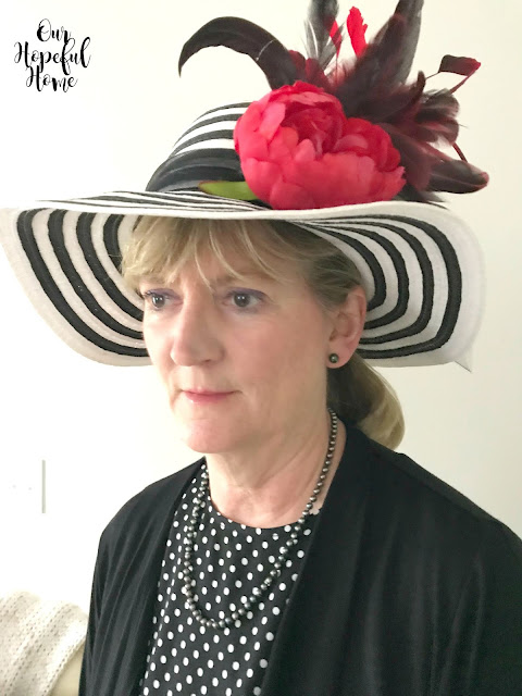 woman wearing straw hat with peony and rooster coque tail feathers