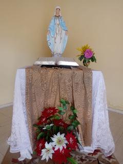 Altar da capela da Comunidade de Aliança com imagem de Maria e Bíblia Sagrada.