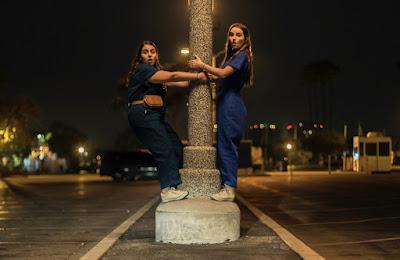 Beanie Feldstein and Kaitlyn Dever on a street lamp in Olivia Wilde's Booksmart (2019)