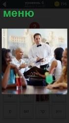 официант принимает заказ по меню у клиентов за столом