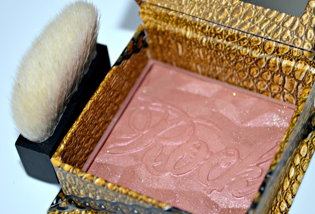 Image of the blusher pan with the blush brush standing next to the box