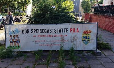 """Plakat der """"DDR-Speisegaststätte Pila"""" mit verfremdeten FDJ-Symbol und drei gezeichneten Figuren in einer Art Pionieruniform."""