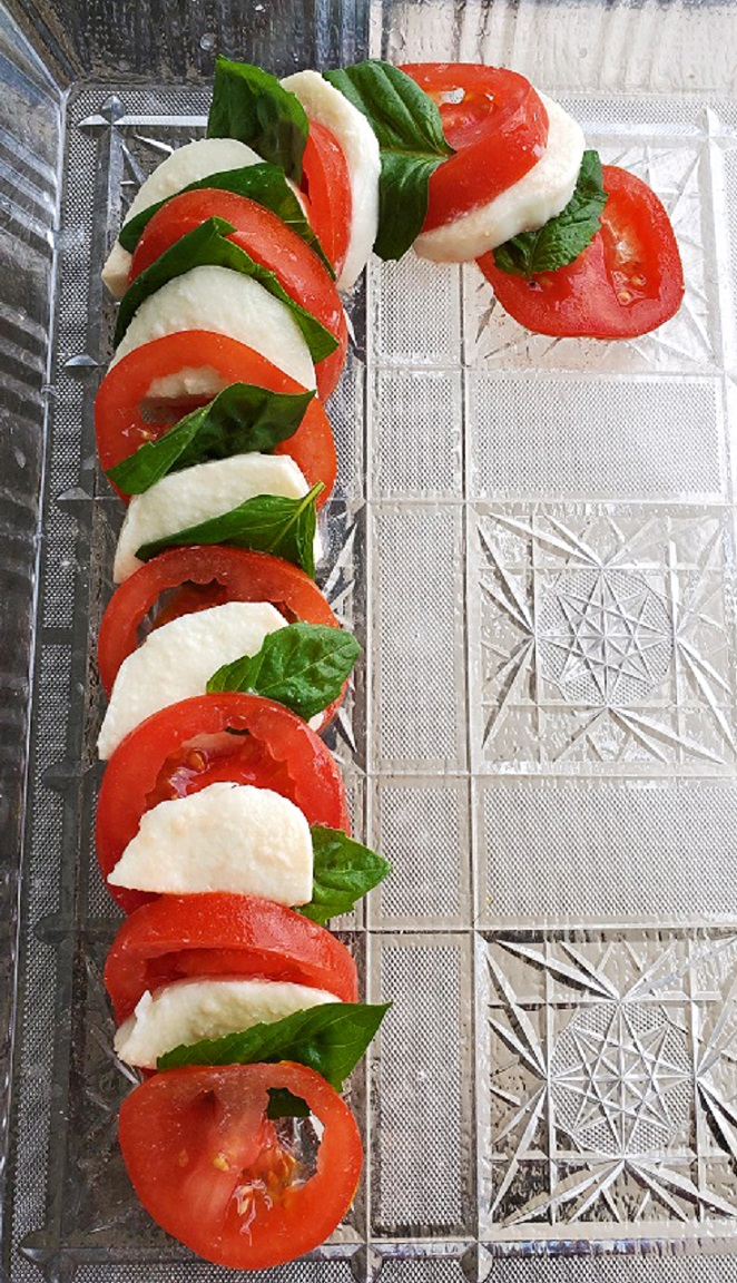 this is a candy cane shaped tomato caprese salad
