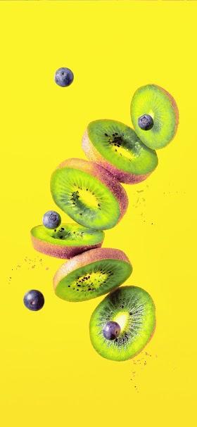 خلفية شرائح فاكهة الكيوي والتوت الصفراء