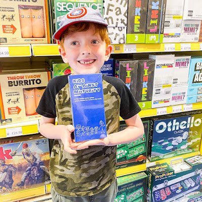 Child holding the boxed game in the shop