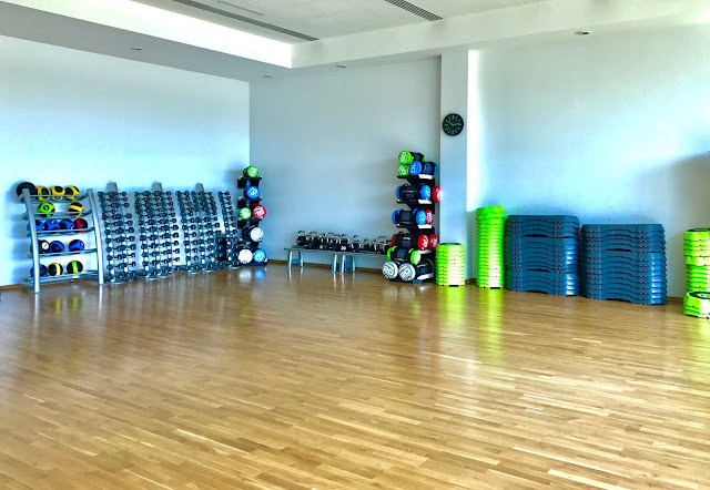 A large studio room with wooden floor and exercise class equipment such as free weights around the outside