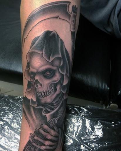 Grim Reaper tatuagem mostrar a sua cara. O reaper é totalmente expondo seu óssea rosto como ele segura a foice e pronto para reivindicar mais almas na calada da noite.
