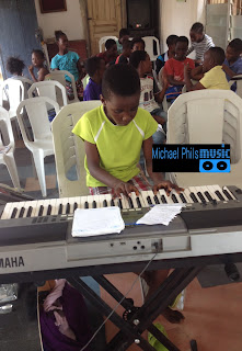 young pianist playing imela by nathaniel Bassey