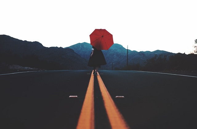 woman in the middle of road with umbrella