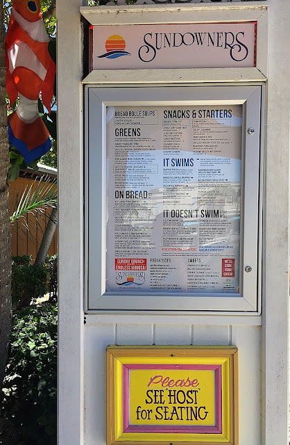 "The menus is displayed outside in a glass case. A sign hangs below that reads, ""Please See Host for Seating."" A clown fish flag hangs from a tree in background."