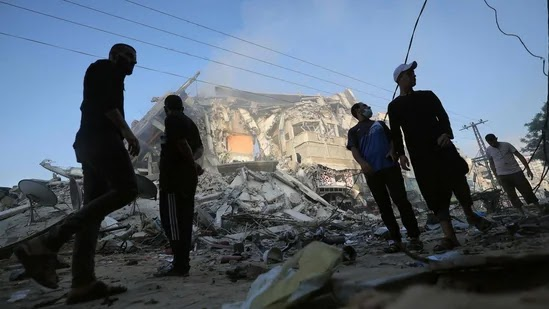 Palestinian men stand amidst debris near the al-Sharouk tower, which housed the bureau of the Al-Aqsa television channel in the Hamas-controlled Gaza Strip, after it was destroyed by an Israeli airstrike, in Gaza City, on May 13, 2021