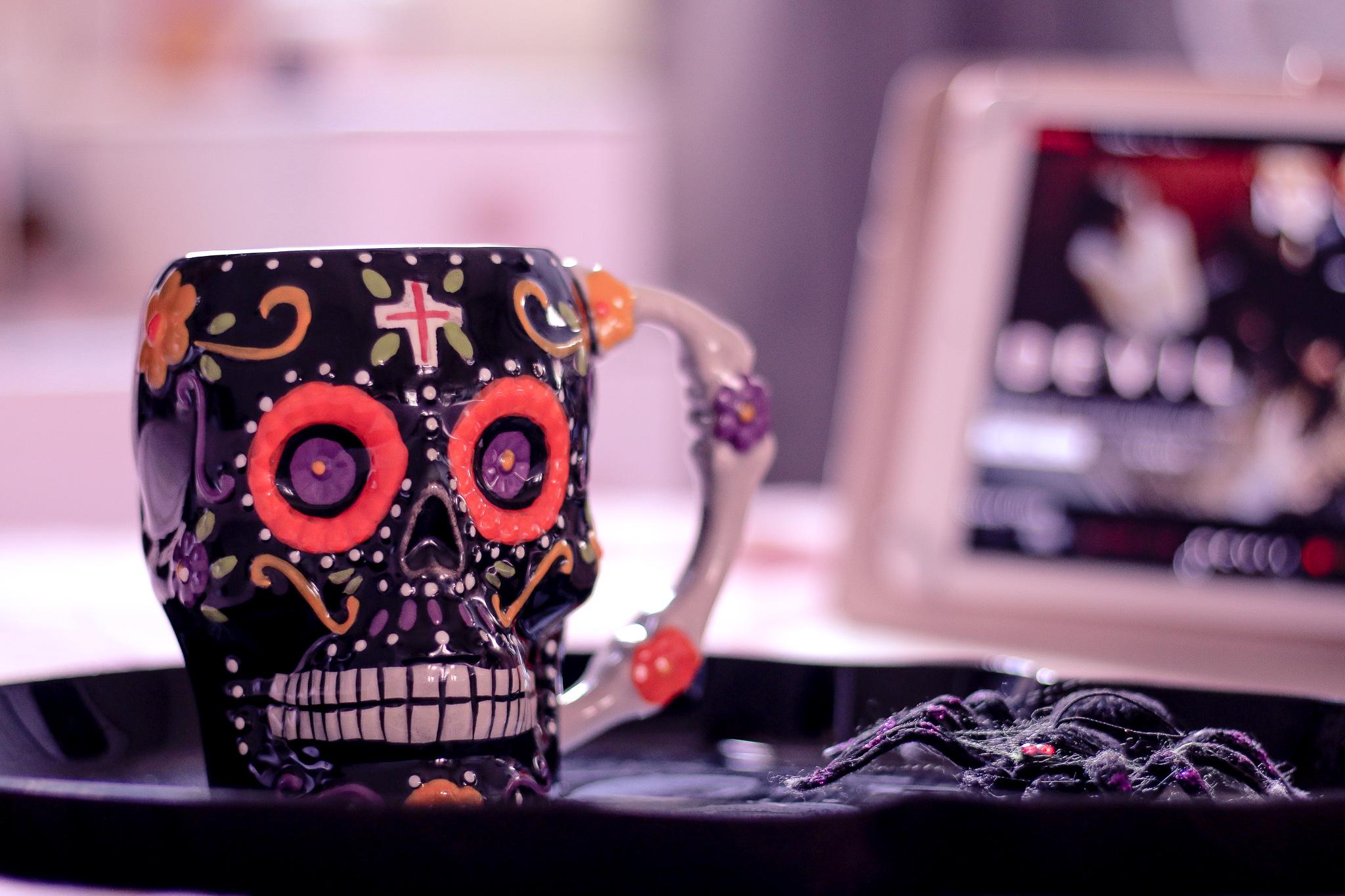 Close up photo of a black and orange sugar skull mug