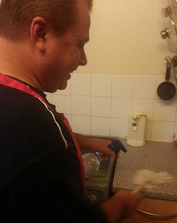 Man Cleaning Kitchen with Pink Apron
