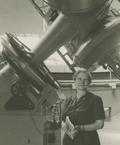 Helen Sawyer Hogg standing in front of a large telescope at the David Dunlap Observatory, University of Toronto. Photo source: University of Toronto Archives