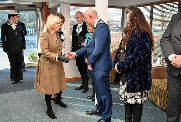 Camilla arrived at the hospice in a smart brown tweed two-piece, pairing the outfit with a simple cream blouse with over-the-knee boots