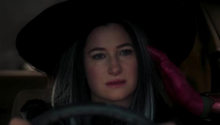 Imagem: a personagem Agnes, vestida de bruxa, olhando para o nada, no volante de um carro e a mão de Visão, vermelha e metálica, encostando na têmpora dela.