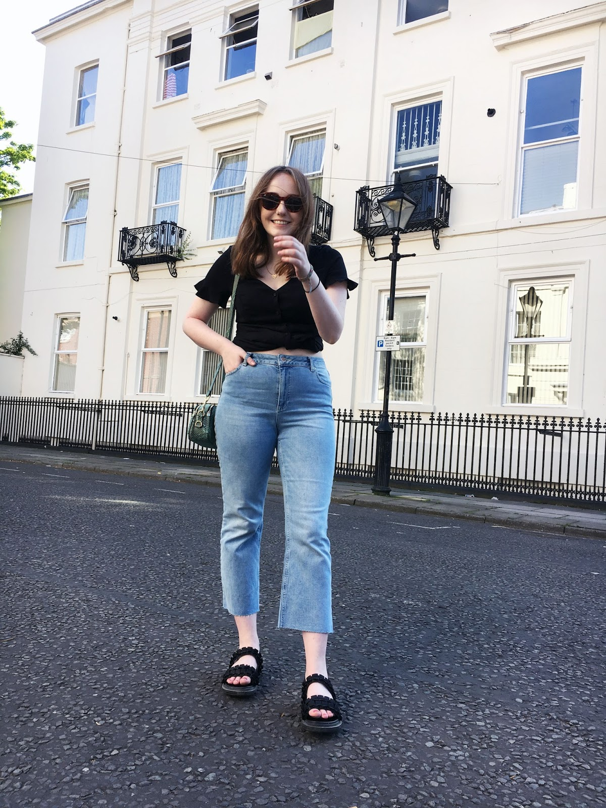 Liverpool based fashion blogger wearing summer outfit of black dress tied into a button up top, light blue kick flare jeans, black chunky sandals and green snake print cross body bag with tortoiseshell sunglasses