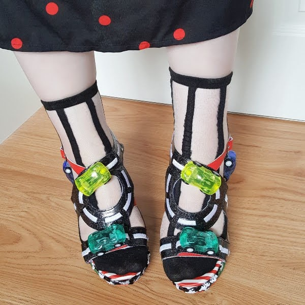 toy cars on straps of shoes on feet