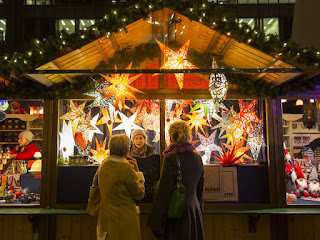 A brightly lit up stall in a market. Two women, with their backs to the camera, are talking to a woman in a booth. Christkindlmarket in Chicago, photo by Jaclyn Rivas
