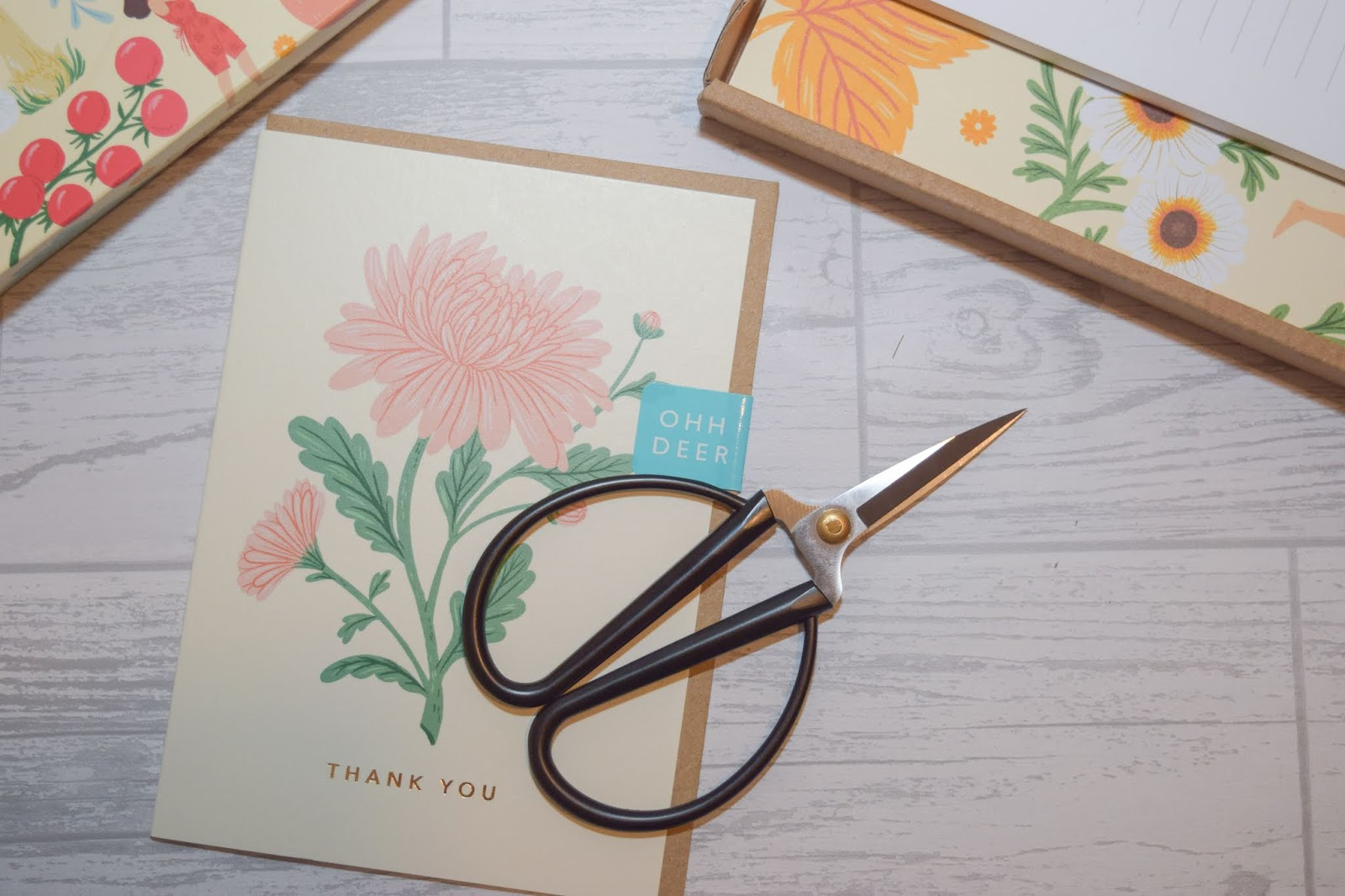 A pair of black scissors with large round handles sitting on a cream thank you card with a pink wildflower on the front.