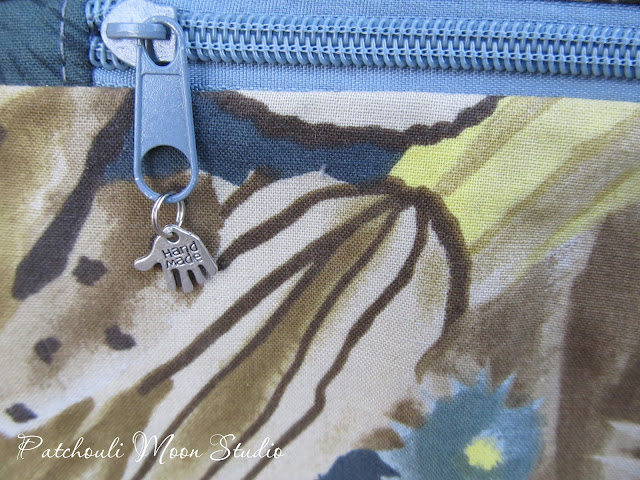 """Closeup of the front zipper pocket showing the zipper pull with a """"handmade"""" charm dangling."""