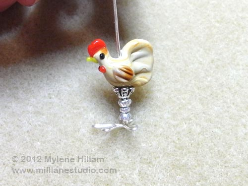 Adding an upturned beadcap, the chicken bead and a silver bicone.