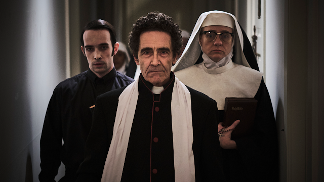 Three people of Catholic leadership walk down a hallway