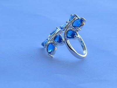Exclusivo anillo de plata con forma de rama con hojas de topacio azul