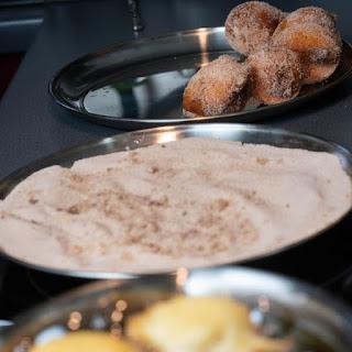 Im Zimt-Zucker gewälzte Quarkbällchen auf einem separaten Teller sammeln