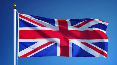Pic of UK's flag flying at top of flagpole against clear blue sky