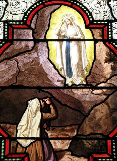 Santa Bernadette imitava todos os gestos de Nossa Senhora. Vitral da Basílica da Imaculada Conceição, de Lourdes