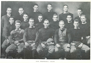 "A black and white photograph of seventeen seated men in dark clothes. One in the front holds a football with ""1915"" painted on it. The photograph is captioned ""1915 Football team."""
