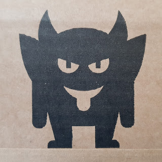 The Dark Imp in black on cardboard box