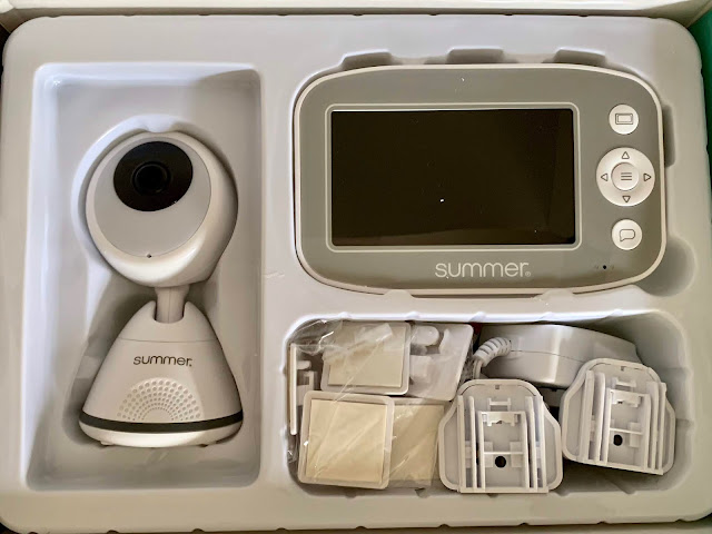 The opened box showing camera, handheld wall attachments and plugs of Summer Pixel Cadet Video Monitor