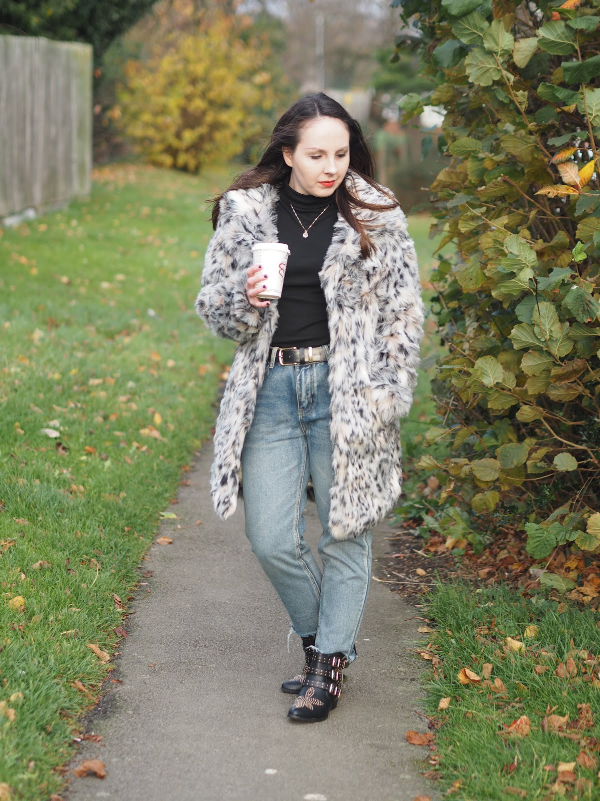 wearing straight leg jeans studded boots and a faux fur coat