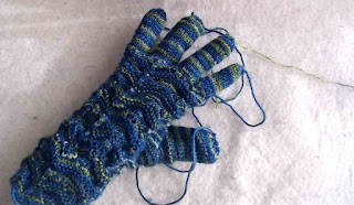 A knit glove with a textured pattern on the back of the hand.  It is knit in variegated dark-green fingering-weight yarn, and there are ends of yarn loose at the tips of the fingers and thumb.