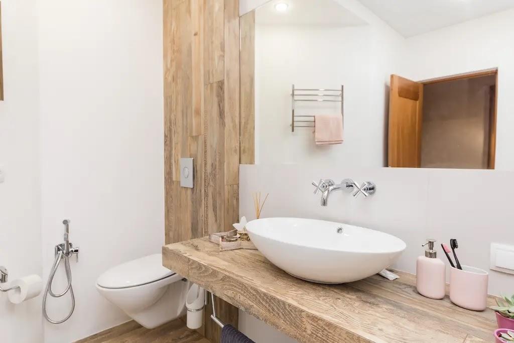 Aseo con alicatado en blanco y detalles en madera natural
