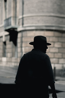 Image of man in the city wearing a fedora.