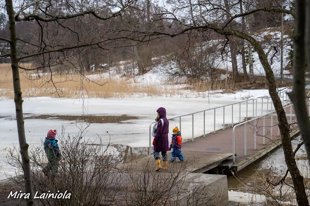 Nainen ja kaksi lasta kuravaatteissa kulkevat Killingholman sillalle