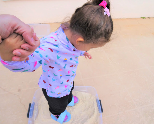 Mom hold daughter's hand as she makes deer footprints in a sandbox with her foam shoes.