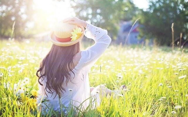 seorang perempuan yang berbahagia duduk di antara rerumputan