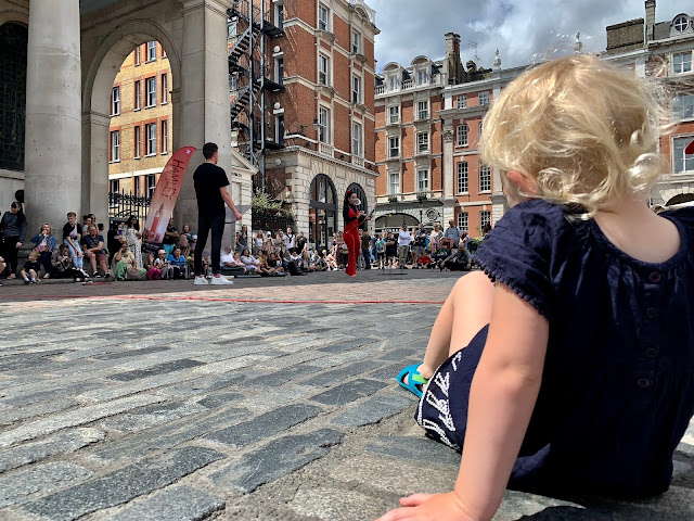 Child sitting on the floor watching street performers in Covent Garden