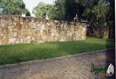 Construção do muro de pedra rústica com o gramado com grama São Carlos, o calçamento com pedra paralelepípedo e as guias de pedra folheta.