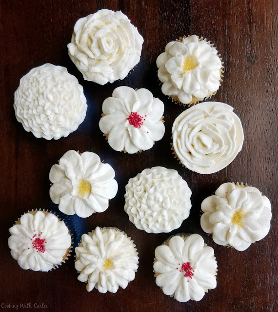 white cupcakes frosted in various flower patterns with italian meringue buttercream