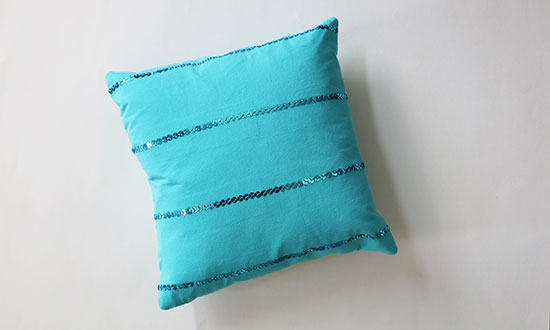 Teal t-shirt throw pillow with sequins set in horizontal stripes, on a white background.