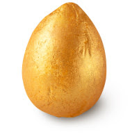 A small golden sparkled egg shaped bath bomb on a bright background