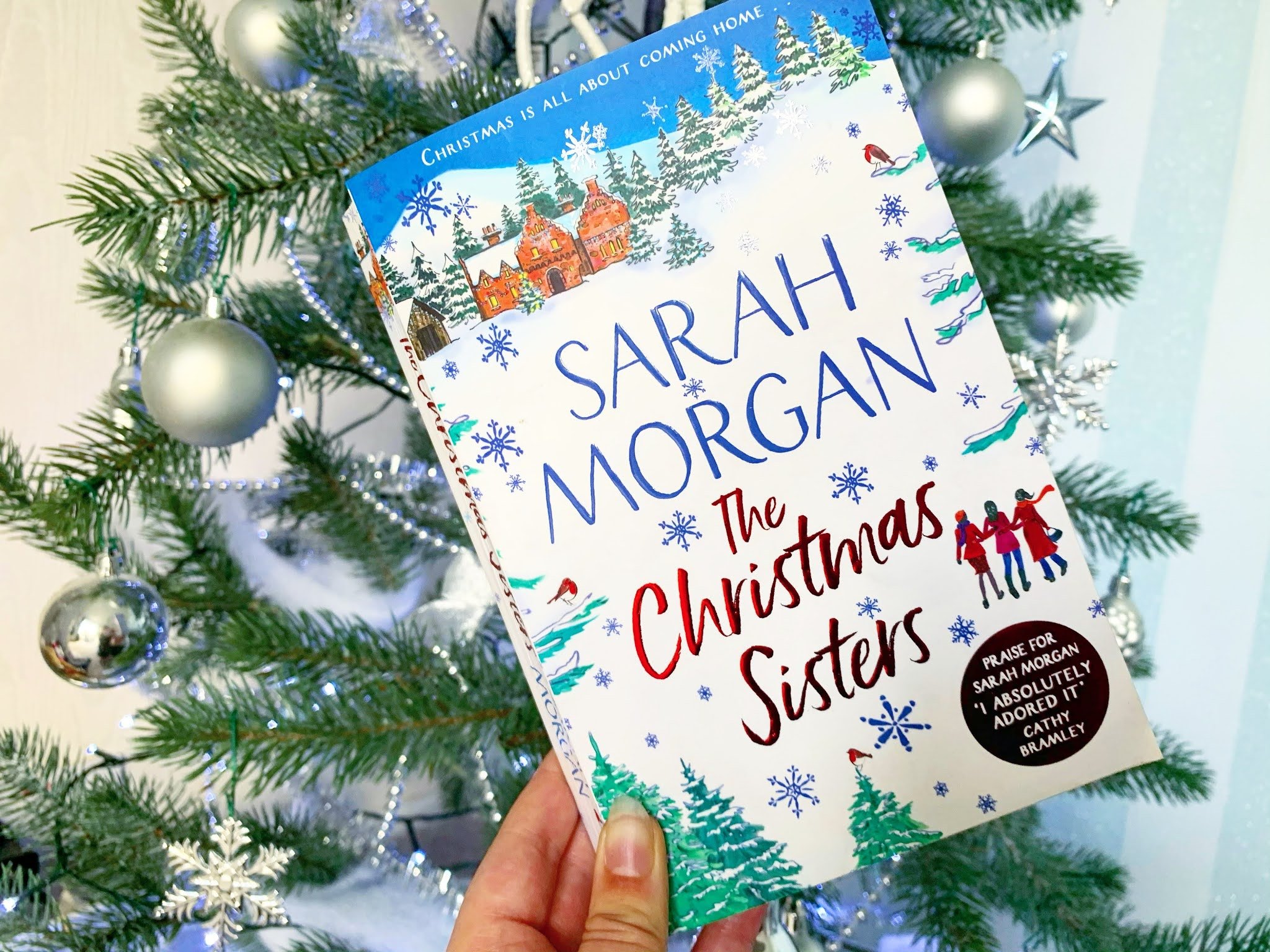 The Christmas Sisters by Sarah Morgan book under the Christmas tree